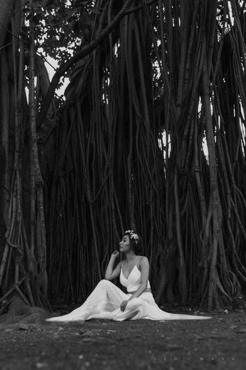 Young woman sitting against banyan tree in forest