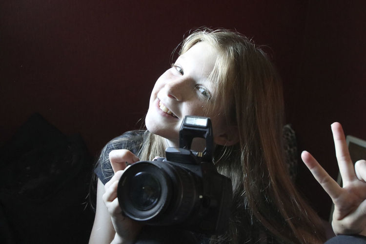 Portrait of girl with camera showing peace sign