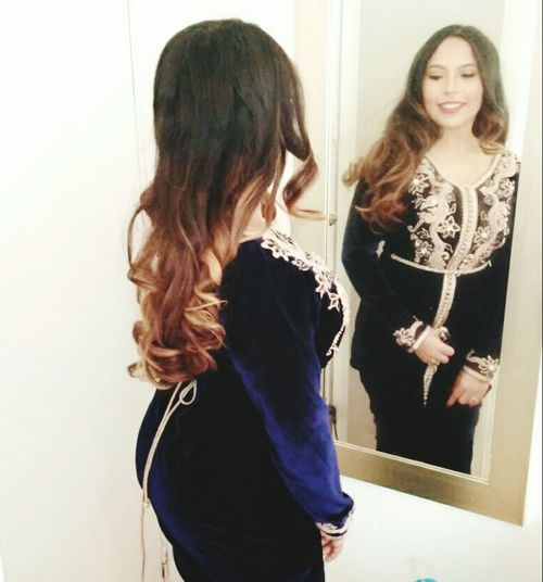 Rear view of woman standing in mirror
