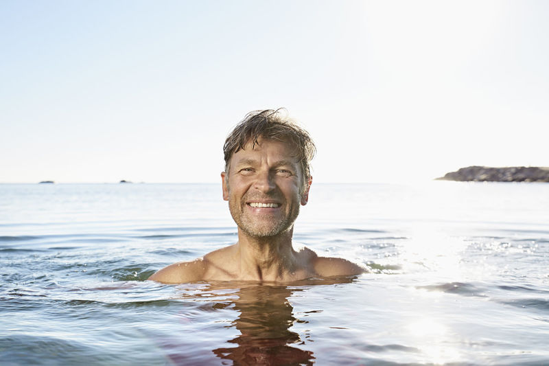 Portrait of happy man in sea against clear sky