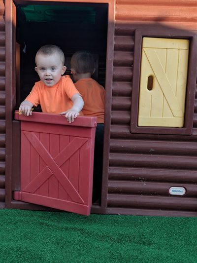 Portrait of cute boy standing in play house