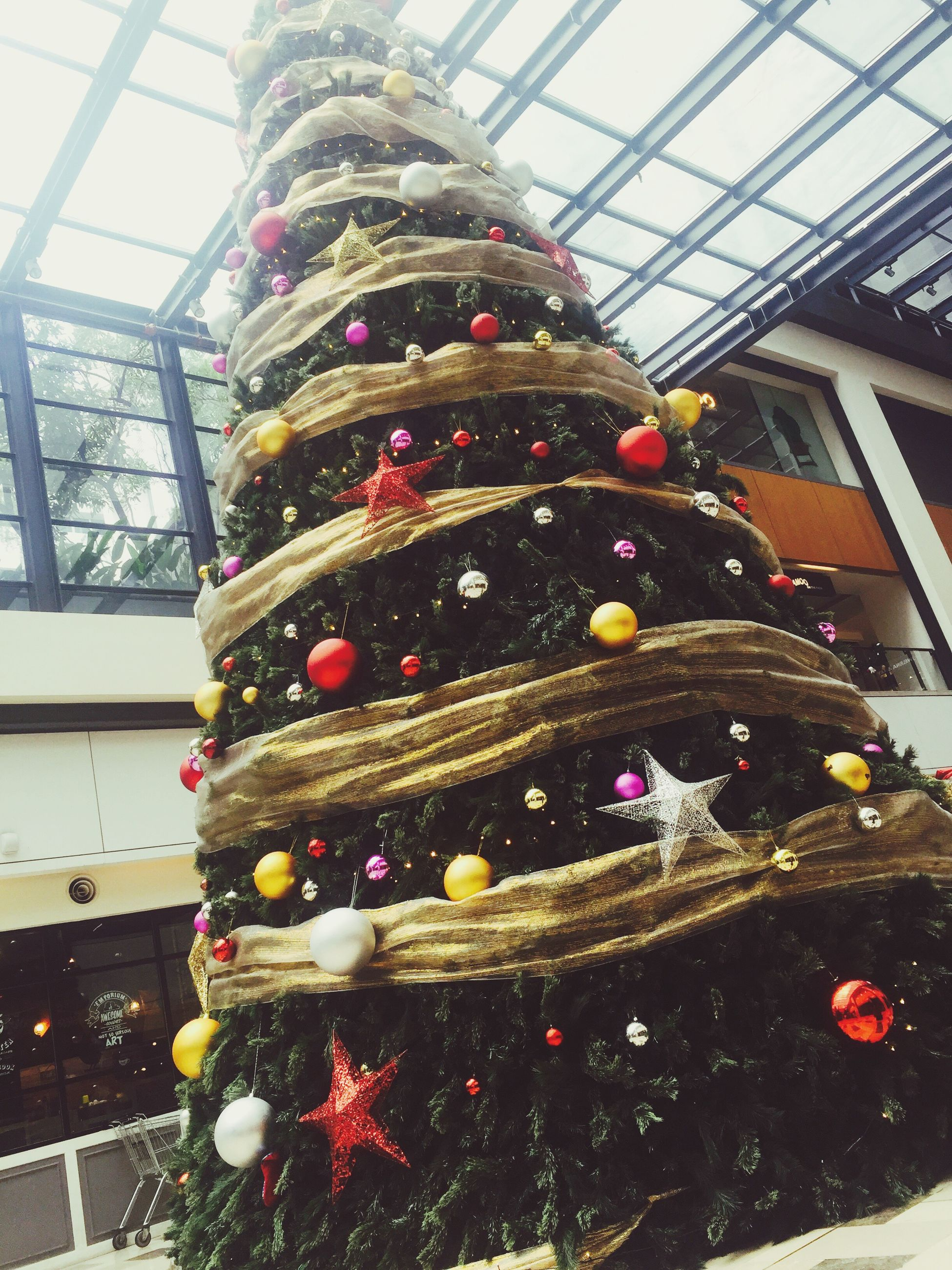 architecture, built structure, building exterior, decoration, art and craft, art, animal representation, incidental people, indoors, glass - material, christmas, sculpture, flower, creativity, day, human representation, celebration, low angle view, christmas tree, city
