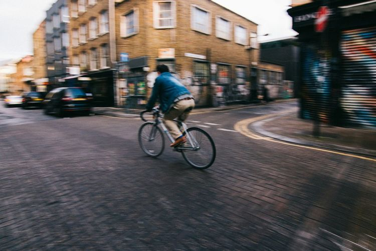 Blurred motion of man riding bicycle on city street