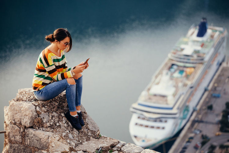 woman using phone and travel cruise chip. high angle view. Authentic Moments Cruise Ship EyeEm Best Shots Panoramic Relaxing Sitting Travel Woman Adult Adventure Aerial View Casual Clothing Chatting Communication Cruise Cruising High Angle View Mobile Phone Montenegro One Person Outdoors Sexygirl Smart Phone Using Phone Wireless Technology