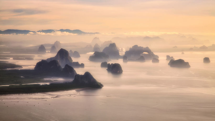 My(i)stery Aerial top view seascape of many silhouette small Limestone or Karst mountains on Andaman sea against the mist and twilight sky during sunrise in Phuket, Thailand. EyeEmNewHere Heaven Airplane Andaman Beauty In Nature Cloud - Sky Day Horizon Over Water Iceberg Idyllic Karst Mountain Mist Nature No People Outdoors Paradise Rock - Object Scenics Sea Sky Sunset Top View Tranquil Scene Tranquility Water
