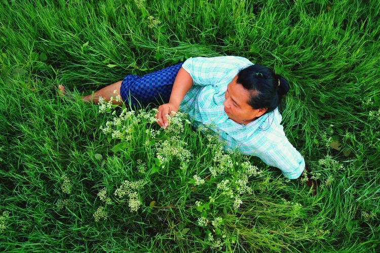 High Angle View Of Woman Sitting On Grassy Field