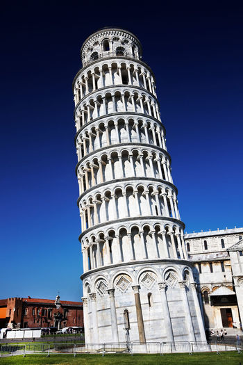 Low angle view of leaning tower of pisa against blue sky