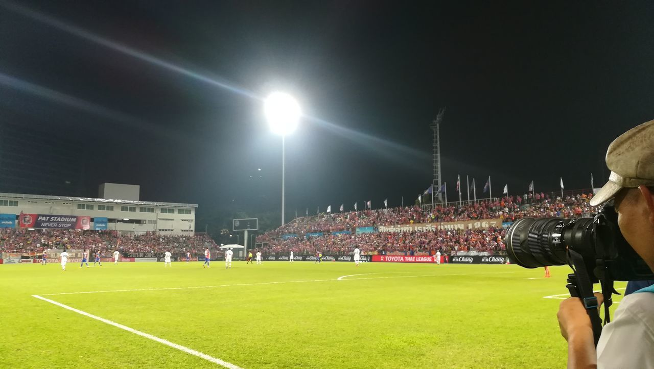 stadium, grass, real people, night, men, floodlight, lighting equipment, spectator, illuminated, large group of people, sport, floodlit, arts culture and entertainment, soccer field, competitive sport, playing field, competition, crowd, photography themes, outdoors, audience, sports event, sportsman, human hand, fan - enthusiast, sky, adult, people