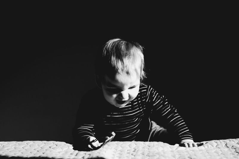 Toddler Boy Climbing On Bed In Darkroom