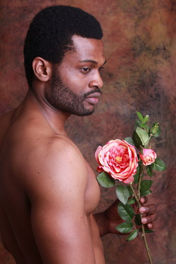 Shirtless Young Man Holding Flower While Standing Against Wall