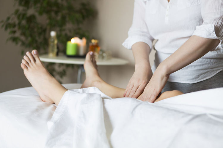 Midsection of woman massaging customer lying on bed