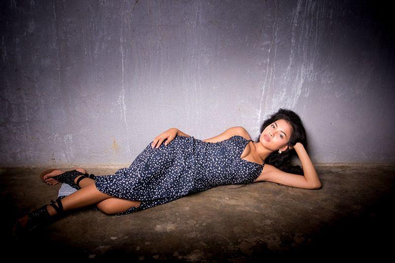 Portrait of beautiful model lying against gray wall
