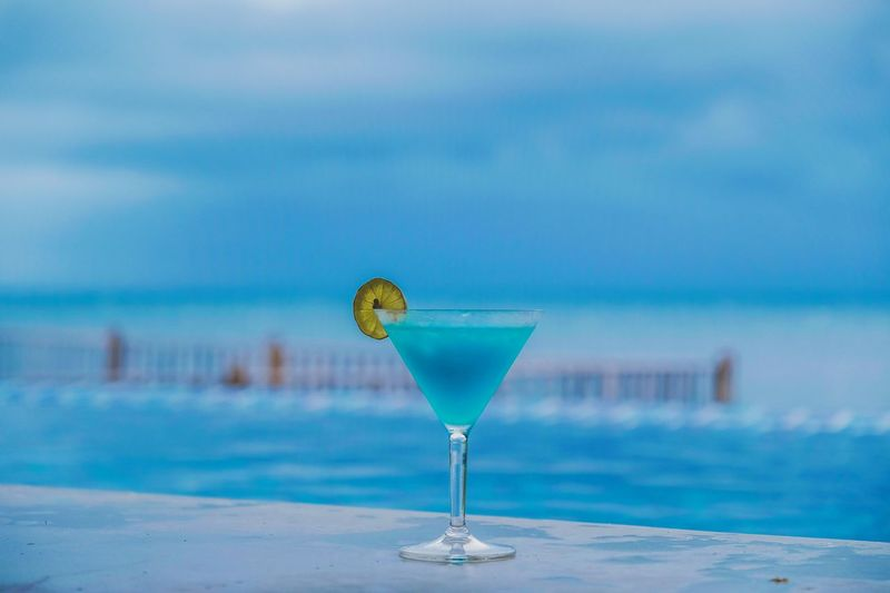 Cocktail against infinity pool and sea