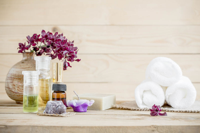 Close-up of scented candles and oils on table