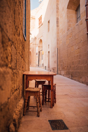 Empty stools and table in alley amidst buildings