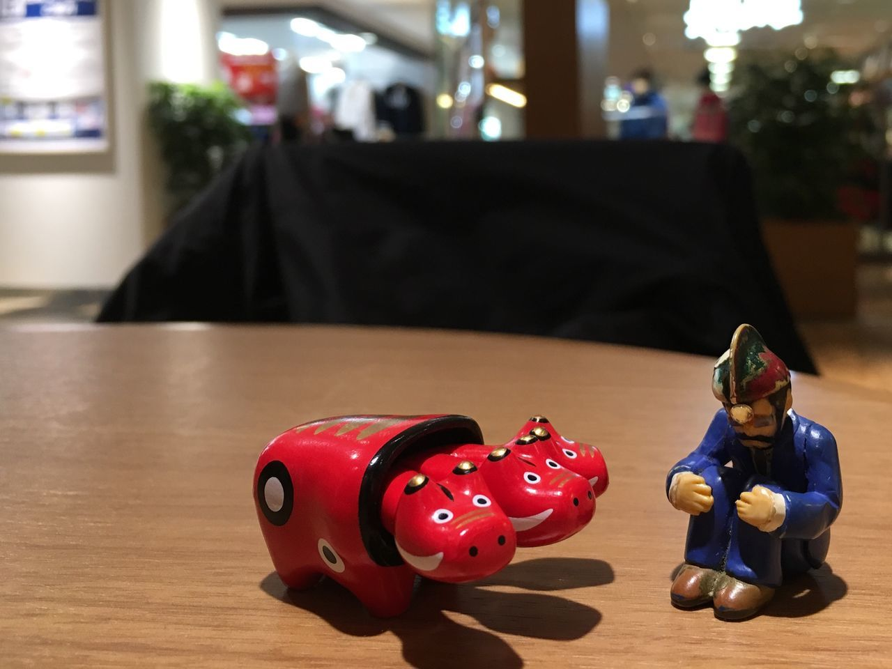 toy, focus on foreground, animal representation, figurine, childhood, indoors, piggy bank, table, no people, close-up, day