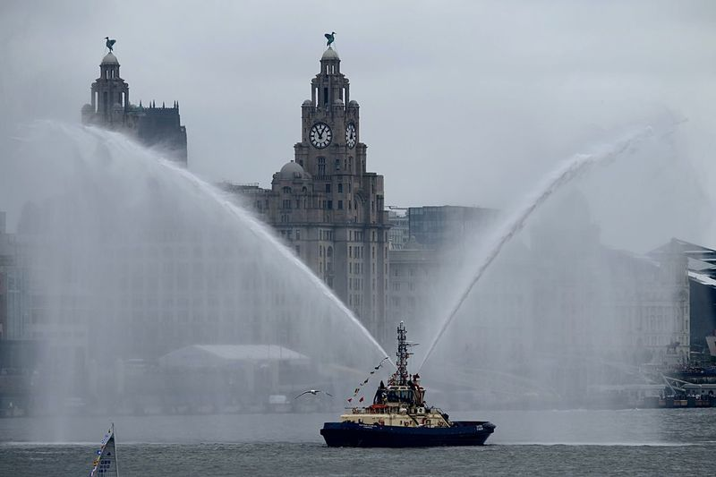 Water Splashing From Tugboat On River Mersey In Front Of Royal Liver Building