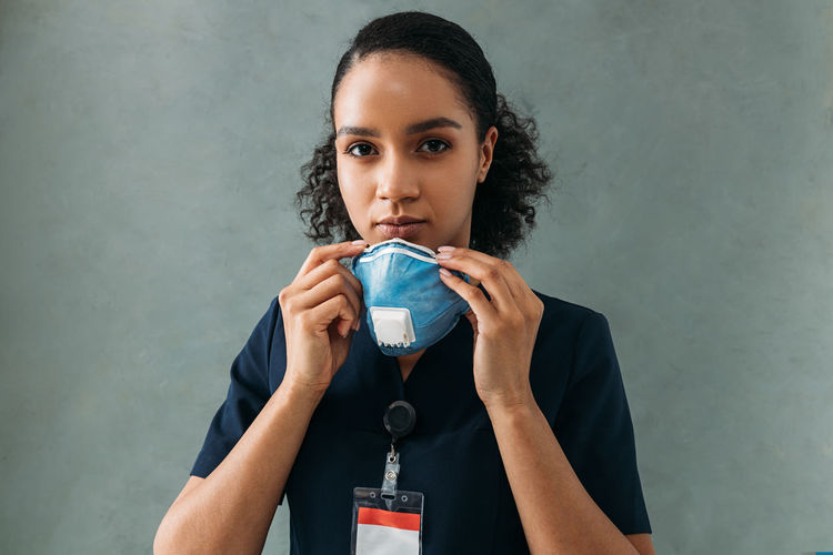 Portrait of beautiful woman drinking water against wall