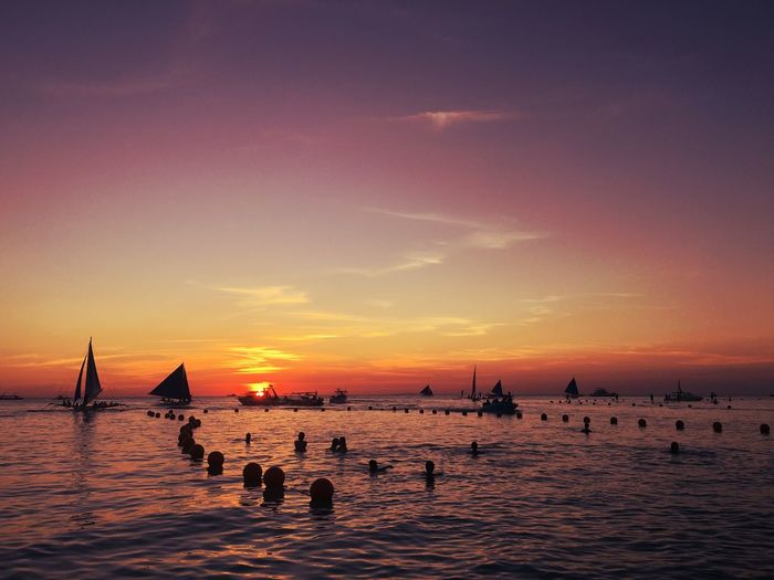 People enjoying in sea against sky during sunset