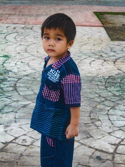 Cute boy standing on footpath