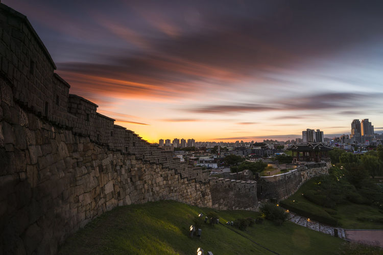 Fortified wall in city against sky during sunset