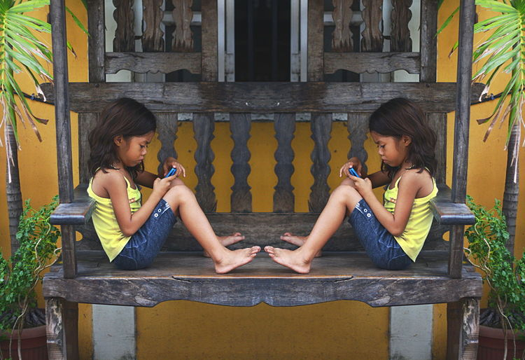 Busy Texting Mirrored Paint The Town Yellow Blue Cellphone Casual Clothing Full Length In Deep Thought Kid Sitting Outdoors Sitting Sitting On A Bench Symmetry Togetherness Vigan Wooden Bench Yellow