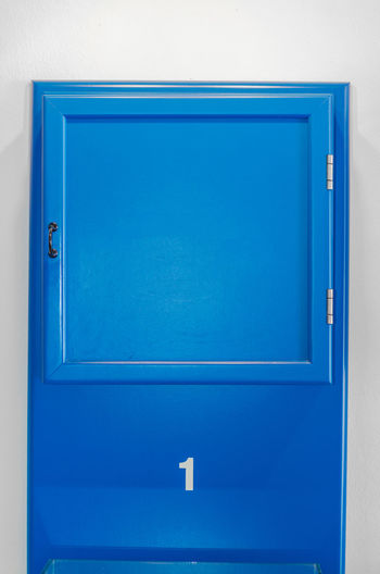 Blue small cabinet door collection with numeral Architecture Blue Box Close-up Closed Communication Container Day Door Entrance Handle Indoors  Metal No People Protection Safety Security Sign Single Object Wall - Building Feature
