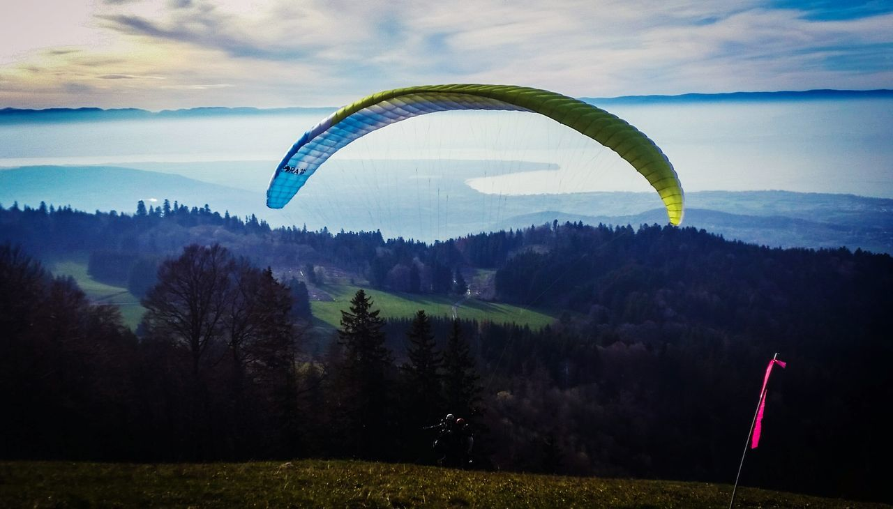 sky, adventure, nature, flying, parachute, landscape, beauty in nature, scenics, tranquility, extreme sports, paragliding, outdoors, tree, mountain, day, no people