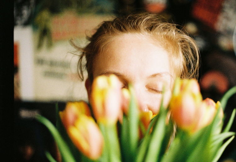 Close-up of smiling woman with tulips