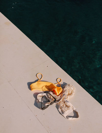 High angle view of personal accessories by sea