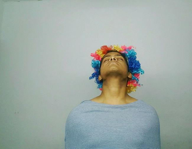 Young man wearing colorful wig while meditating against gray background