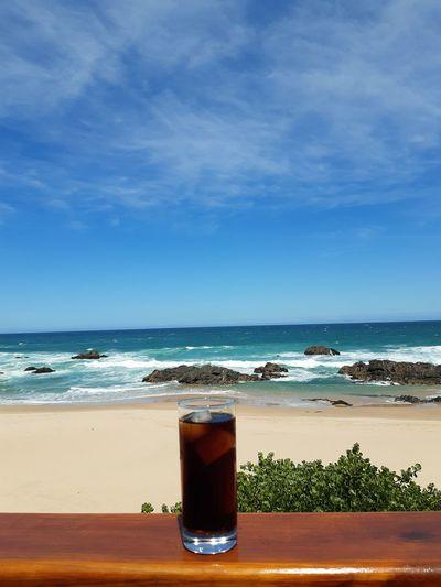 Glass of coffee on beach against sky