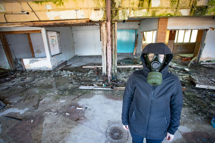Full length portrait of man standing in abandoned building