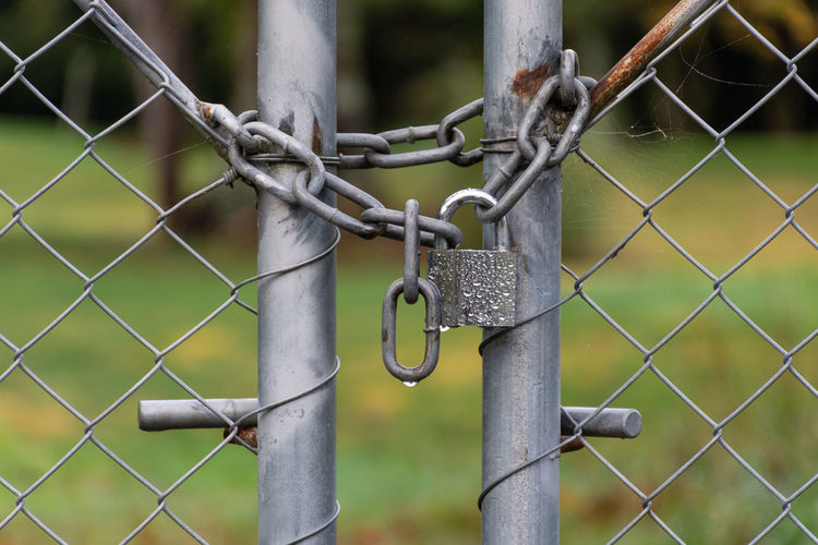 Close-up of chain hanging on chainlink fence