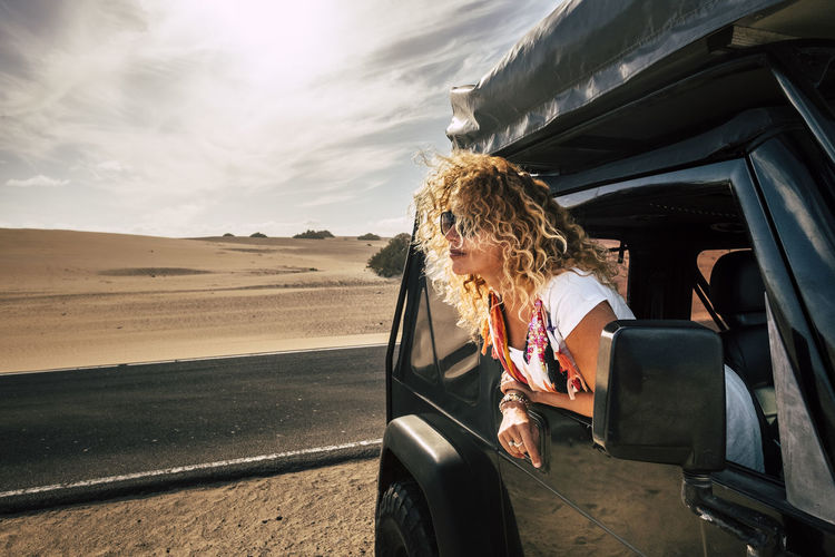 Woman with blond hair looking through window while traveling in off-road vehicle