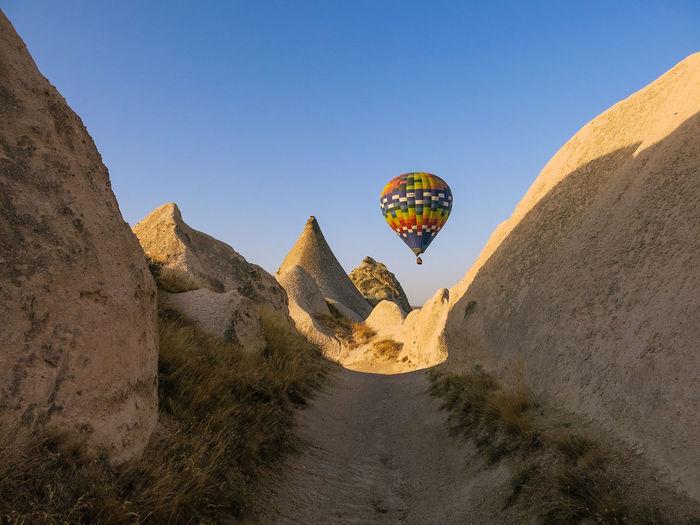 Hot air balloon flying over rock formations in cappadocia