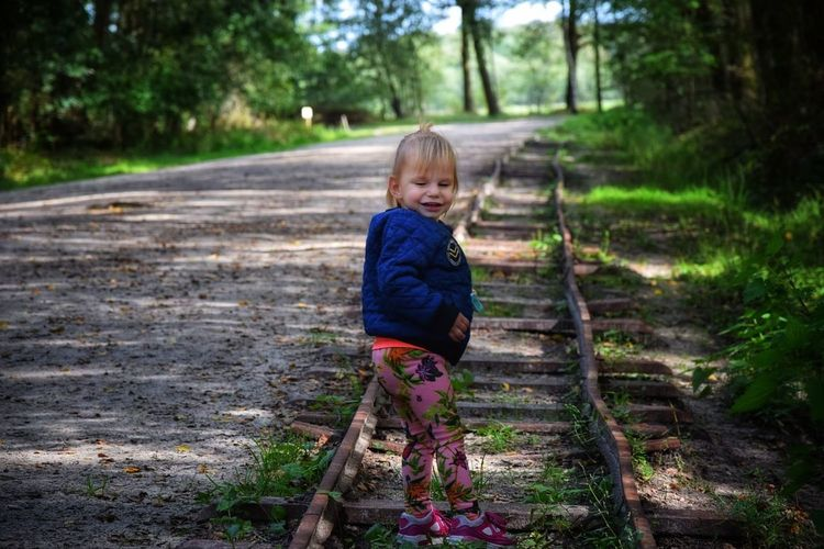 Side View Of Cute Baby Girl Standing On Railroad Track