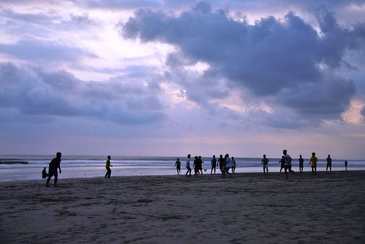 Male friends playing soccer at beach against cloudy sky