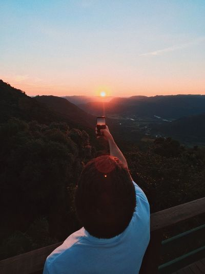 Rear view of man using smart phone against sky during sunset