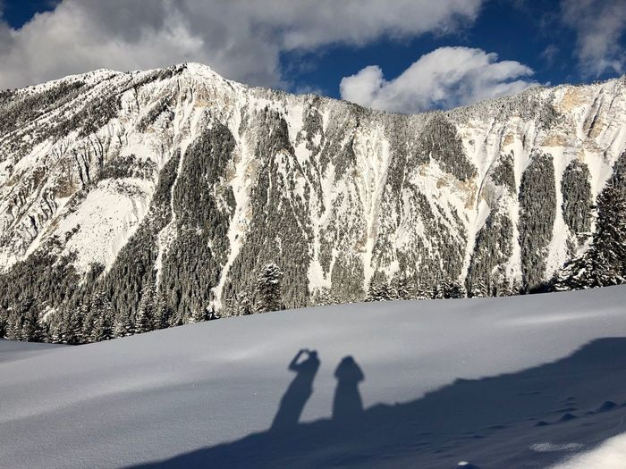 Shadow of people on land against snowcapped mountains