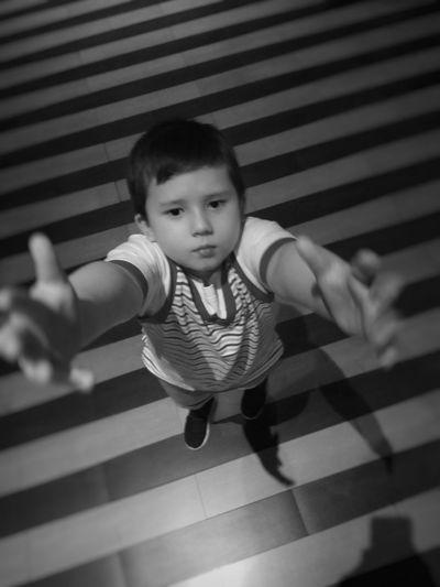 High angle portrait of boy standing on tiled floor
