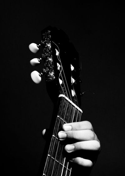 Cropped Hand Playing String Instrument Against Black Background
