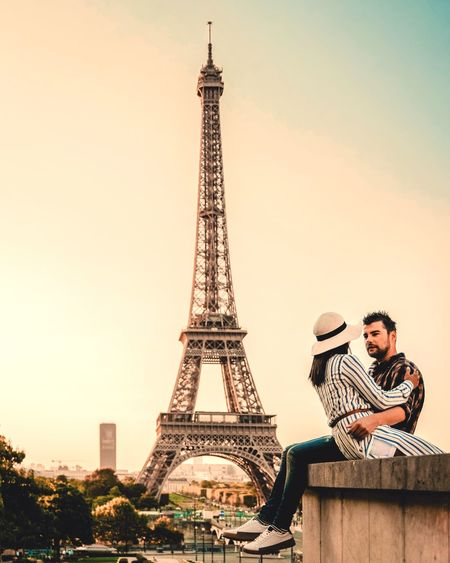 Couple romancing while sitting on retaining wall against eiffel tower during sunset