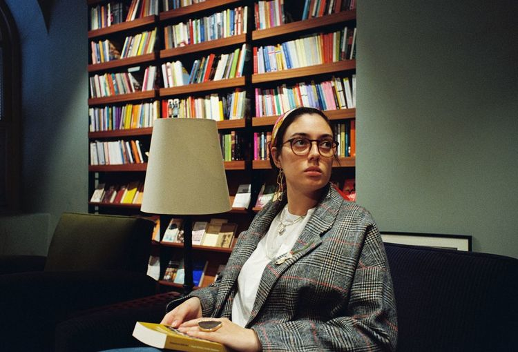 Woman looking away while sitting in library