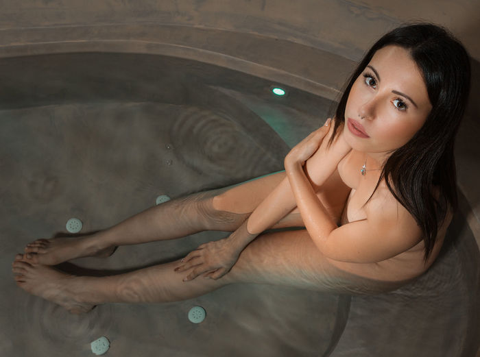 High angle view portrait of young woman sitting in hot tub