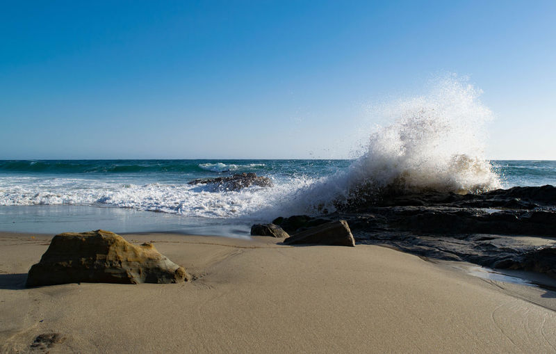 Wave splashing on rock formation at beach against clear sky