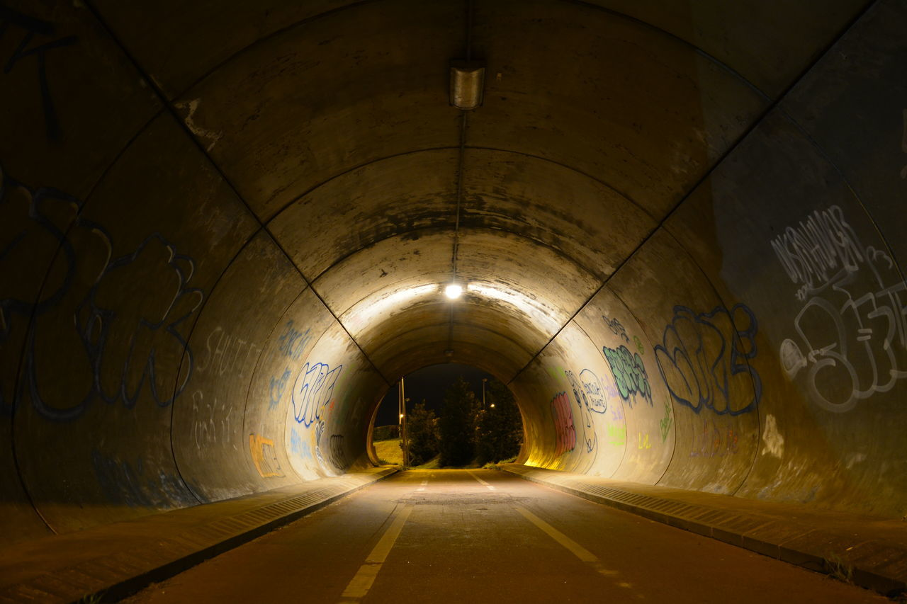 Empty road in illuminated tunnel at night