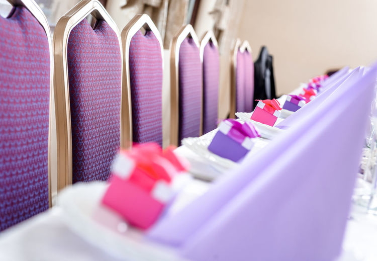 Empty chairs and wedding table decorations Banquet Celebration Empty Chairs Event Holiday Restaurants Setting Table Setting Wedding Celebration Event Chairs Close-up In A Row Large Group Of Objects No People Nobody Pink Color Place Card Purple Restaurant Selective Focus Table Violet Wedding Ceremony Wedding Day