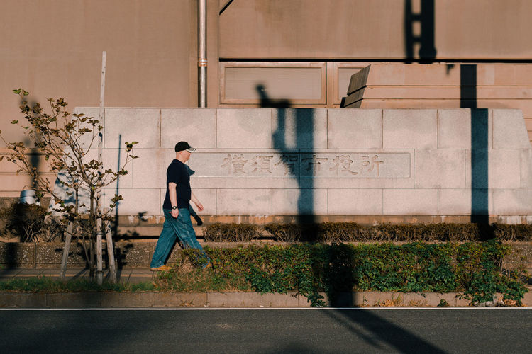 Side view of man walking against wall