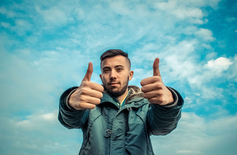 Portrait of young man showing thumbs up sign against cloudy sky